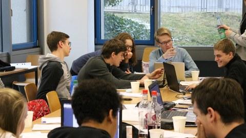 Foto von Studierenden während der Teamarbeit. Sie sitzen an einem Tisch und arbeiten an Laptops oder unterhalten sich.