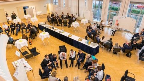 Foto eines großen Saales von oben. In vier großen Stuhlkreisen sitzen Menschen und unterhalten sich. In der Mitte des Saales ist ein Buffet aufgebaut.