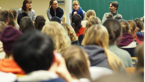 Foto von einer Gruppe von Studierenden von hinten gesehen. Vor ihnen sitzen vier Referenten und Referentinnen auf Stühlen und sprechen mit dem Publikum.