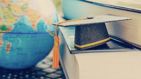 Foto von einer Tastatur auf der verschiedene Gegenstände liegen. Links im Bild befindet sich ein Globus. Rechts liegen zwei dicke Bücher ein wenig verschoben übereinander. Zudem liegt ein kleiner Doktorhut auf dem unteren Buch.
