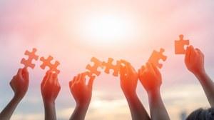 Darstellung von sechs Armen, die von unten aus dem Bild kommend ihre Hände in die Luft strecken und dabei jeweils ein großes Puzzleteil halten. Über ihnen ist verschwommen die Sonne zu erkennen.