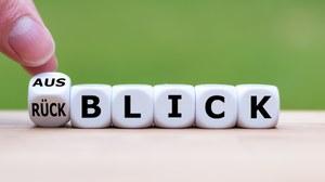 """Abbildung von sechs nebeneinander liegenden Würfeln. Auf dem ersten Würfel steht auf zwei Seiten """"Aus"""" und """"Rück"""", auf den anderen Würfeln die Buchstaben """"B"""", """"L"""", """"I"""", """"C"""", """"K"""""""