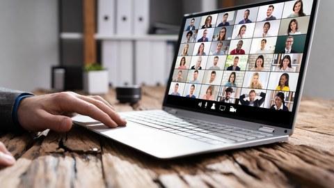 Foto eines Laptops auf einem Holztisch. Auf dem Display erkennt man in einem Raster sehr viele Gesichter, wie bei einer Videokonferenz. Eine Hand ist zu sehen, die das Touchpad des Laptops bedient.
