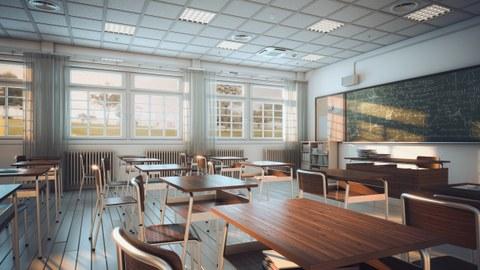 Foto eines Klassenzimmers. An freistehenden kleinen Holztischen steht jeweils ein Holzstuhl. Licht fällt durch die Fenster, die sich gegenüber des Betrachtenden befinden. An der rechten Wand befindet sich eine große und voll beschriebene Tafel.
