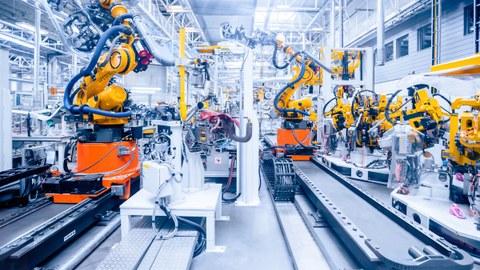 Foto einer großen Halle einer Autofabrik. Auf kurzen Schienen befinden sich große Roboter.