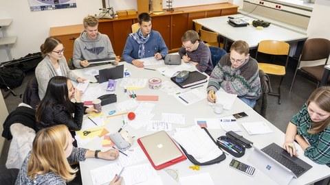 Foto von einer Gruppe Studierender. Sie sitzen um einen großen Tisch und arbeiten an Laptops oder schreiben auf Papier. Auf dem Tisch liegen viele unterschiedliche Arbeitsmaterialien wie Stifte, Blätter und Taschenrechner.