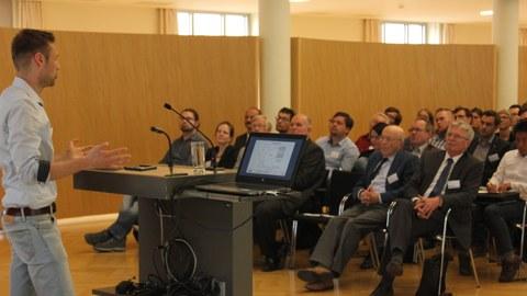 Foto eines Salles. Links im Bild steht hinter einem Pult ein Mann und hält eine Rede. Vor ihm im Raum sitzen viele Personen auf Stuhlreihen und hören ihm zu.