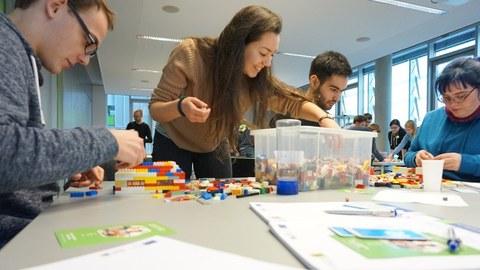 """Foto einer Gruppe Studierender. Sie sitzen um einen Tisch herum und basteln mit Lego im Zuge des Workshops """"Agile meets Lego""""."""