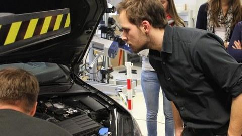 Foto eines Studenten, der unter die Motorhaube eines Autos schaut. Im Hintergrund sind zwei Studentinnen zu erkenne, die auch in das offene Auto blicken.