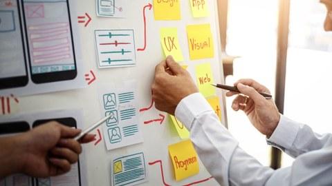Foto eines Whiteboardes, welches mit verschiedenen Post-it Notes beklebt ist. Die Hände von zwei Personen bekleben und beschriften das Whiteboard.