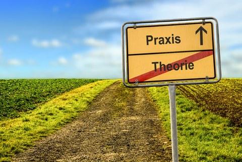 """Darstellung eines Wegweisers, der auf einem Feldweg steht, der geradeaus zum Horizont führt. Der Wegweiser ist horizontal geteilt. Oben steht """"Praxis"""" mit rechts daneben einem geraden Pfeil. Unten ist das Wort """"Theorie"""" durchgestrichen."""