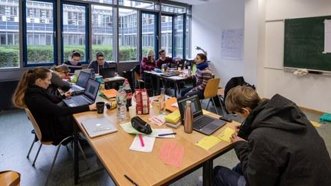 Foto von Studierenden, die an drei zusammengeschobenen Tischgruppen sitzen und an ihren Laptops arbeiten oder etwas auf Papier aufschreiben.