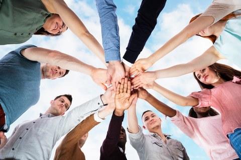 Zwölf im Kreis stehende Personen legen ihre Hände in der Mitte des Kreises übereinander