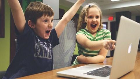 Auf dem Foto sitzen ein Junge und ein Mädchen vor einem Laptop und jubeln und freuen sich.