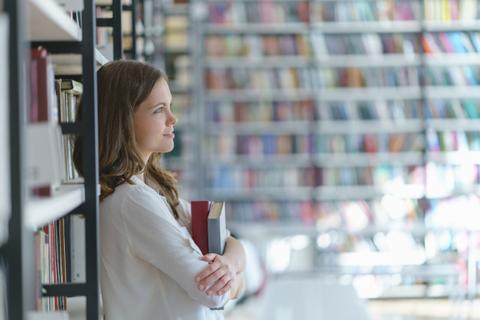 Foto einer Studentin in einer Bibliothek. Sie lehnt mit dem Rücken an einem Bücherregal und hält zwei Bücher in den verschränkten Armen.