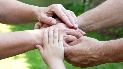 five hands on top of each other; among them hands of children and of elderly persons