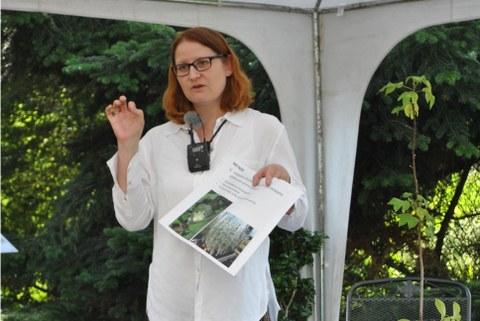 Foto von Katharina Stein während ihres Vortrages. In einer Hand hält sie Bild von Pflanzenteilen mit Beschriftung, die andere Hand gestikuliert.