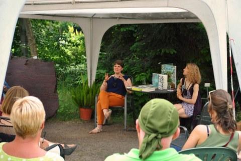 Foto: Solvejg Nitzke sitzt mit der Moderatorin Lilith Diringer an einem Tisch mit Büchern unter einem Pavillon. Vier Zuhörer:innen sehen sie an.