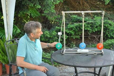 Dr. Michael Kobel setzt ein Pendel, das mit zwei weiteren Pendeln gekoppelt ist, in Schwingung.