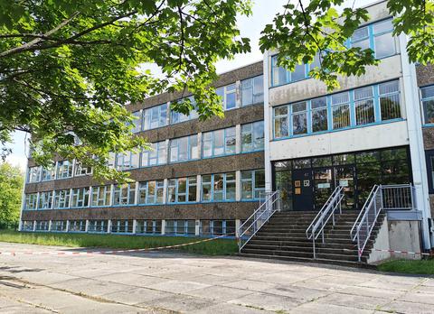 Teilansicht eines großen, dreistöckigen Gebäudes mit langen blau gerahmten Fensterreihen und dunkler Eingangstür zu der eine Treppe führt. Der Platz vor der Treppe ist mit rot-weißem Absperrband abgesperrt.