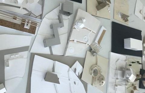Verschiedene Architekturmodelle auf einem Tisch.