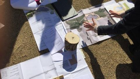 Foto zeigt auf dem Boden augebreitete Pläne, Skizzen und technischen Zeichnungen. Eine Lehrperson erklärt diese, während die Studenten darum verteilt stehen.