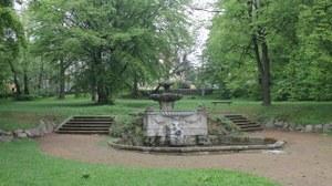 Bild zeigt die Brunnenanlage im Gutspark Gönnsdorf. An der Brunnenanlage führt jeweils eine Treppe linker und rechter Hand vorbei, die in die großräumige Wiesenfläche münden.