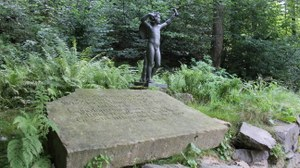 Foto zeigt die Plastik Amor im Seifersdorfer Tal. Vor der Plastik ist eine Steintafel mit Inschriften platziert, die von einer wilden Krautschicht umgeben ist.