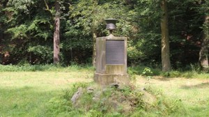 Foto zeigt den Tempel der Freundschaft im Seifersdorfer Tal. Er besteht aus aus einer Säule auf der eine Vase platziert ist.
