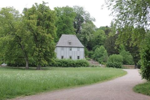 Foto von Goethes Gartenhaus im Ilmpark in Weimar. Dieses ist umgeben von Gehölzen.
