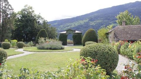Foto zeigt den Schlosspark Ortenstein in der Schweiz. Das Wegenetz bildet ein Rondell, welches bepflanzt ist. Auf dem Rasen sind geschnittene Buchsbäume angeordnet.