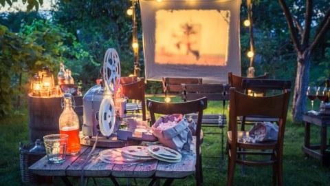 Zu sehen sind eine Leinwand, Stühle sowie ein altes Filmgerät.