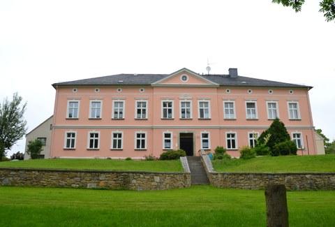 Foto zeigt das Pfarrhaus in Crostwitz, welches über eine Treppe über die Wiesenfläche erreichbar ist.