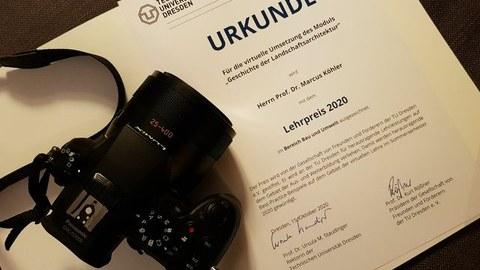 Zu sehen ist die Urkunde des Lehrpreises, daneben eine Kamera.