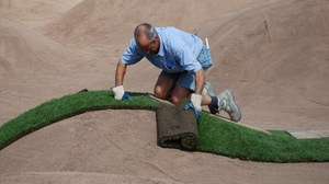 Ein Mann verlegt Rollrasen auf modelliertem Boden.