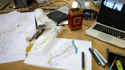 typischer Arbeitsplatz von Studierenden der Landschaftsarchitektur mit Skizzienpapier, Stiften und Computer