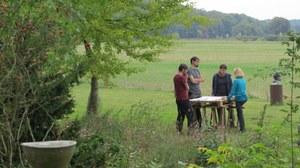 Foto von vier Personen auf einer Wiese, die an einem Tisch arbeiten