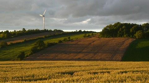 Diese Abbildung zeigt ein Foto einer landwirtschaftlich geprägten Landschaft bei gewittriger Stimmung.