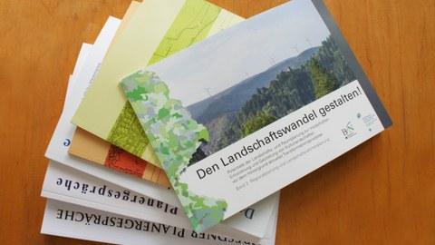 Das Foto zeigt eine Auswahl der erschienen Forschungsarbeiten der Professur für Landschaftsplanung auf einem Tisch liegend.