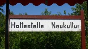 """Das Bild zeigt ein Foto einer Bahnhaltestelle mit der Aufschrift """"Haltestelle Neukultur""""."""