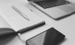 Foto mit Laptop, Stift, Notizbuch und Handy auf einem Schreibtisch