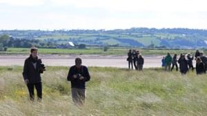Foto von Studierenden auf einer Exkursion in Irland, welche über eine grüne Wiese gehen.