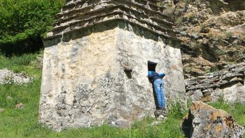 Foto einer Person, die ihren Kopf in ein historisches Steinhäusschen steckt und sich darin umblickt.