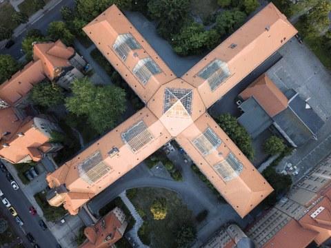 Auf dem Bild ist der Hülße-Bau von oben zu sehen mit seiner markanten kreuzförmigen Architektur und rotem Dach.