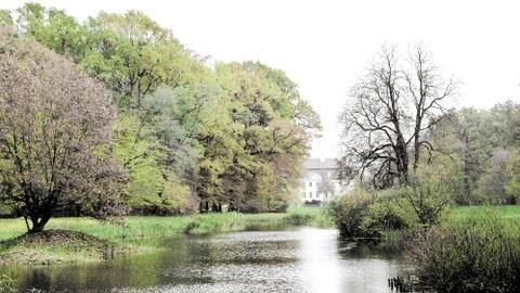 Foto eines Landschaftspark mit Fluss und Herrenhaus dahinter