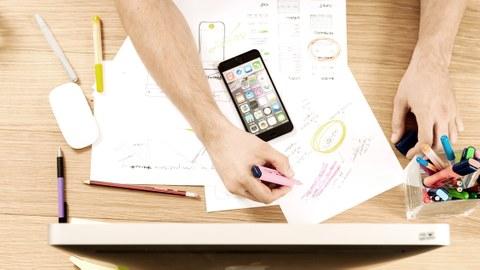 Foto auf einen Arbeitsplatz von oben gesehen mit Bildschirm, Handy, Papier und Stiften