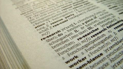 """Das Foto zeigt die Seite eines aufgeschlagenen Wörterbuchs. Im Zentrum des Bildes steht das Wort """"research""""."""