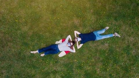 Studierende mit Maske liegen auf einer Grünfläche