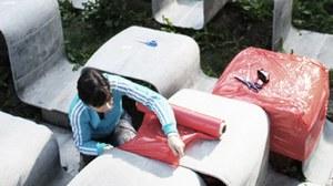 Foto einer Studierenden die Betonmöbel in rote Folie einpackt