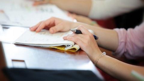Foto von den Händen einer Studierenden mit einem Notizheft und Stift